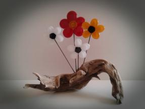 Blomster i glas på drivtømmer
